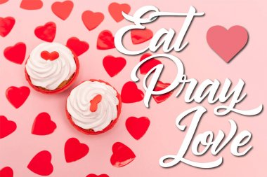 Top view of red hearts and cupcakes near eat pray love lettering on pink stock vector