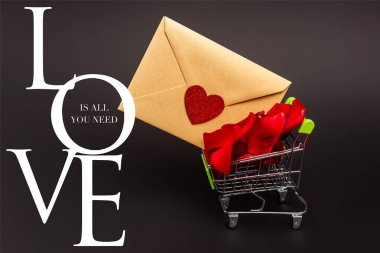 Toy shopping cart with rose petals and envelope near love is all you need lettering on black stock vector