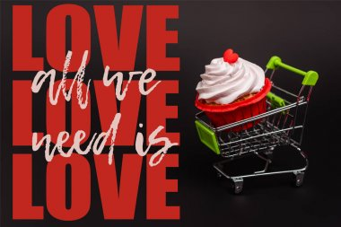 Small shopping cart with valentines cupcake near all we need is love lettering on black stock vector