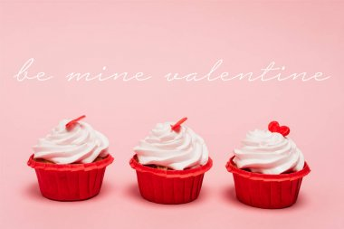 Valentines cupcakes with red hearts near be mine valentine lettering on pink background stock vector