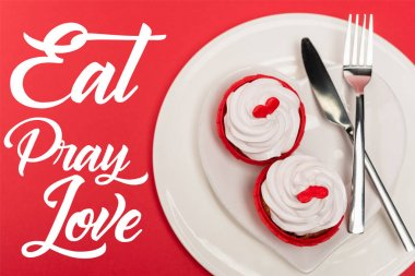 Top view of cupcakes on plate with cutlery near eat pray love lettering on red background stock vector