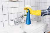 Fotografie Ausgeschnittene Ansicht einer Frau in Gummihandschuhen, die eine Flasche Waschmittel in der Nähe von Waschbecken und Fliesen im Badezimmer hält