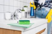Grüner Lappen und Schwamm auf Waschbecken in der Nähe einer Frau in Gummihandschuhen reinigen Badezimmer auf verschwommenem Hintergrund