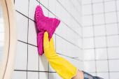 Fotografie Ausgeschnittene Ansicht einer Frau in Gummihandschuhen, die Fliese mit Lappen in der Nähe von Spiegel auf verschwommenem Vordergrund im Badezimmer reinigt
