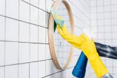 Oříznutý pohled na ženu čistící zrcadlo s čisticím prostředkem a hadrem v moderní koupelně
