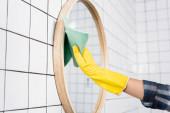 Fotografie Ausgeschnittene Ansicht einer Frau im Gummihandschuh, die beim Putzen des Badezimmers Spiegel mit Lappen wischt