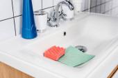 Fotografie Schwamm und Lappen im Waschbecken neben Wasserhahn im Badezimmer