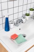 Lahvička čisticího prostředku v blízkosti houby a hadru v umyvadle v moderní koupelně