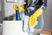 Oříznutý pohled na ženu v gumových rukavicích čištění notebook s hadrem a držení saponátu na rozmazaném pozadí