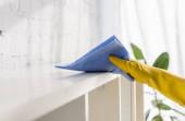 Oříznutý pohled na osobu v gumové rukavice čisticí skříň s hadrem doma