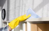 Ausgeschnittene Ansicht einer Frau, die während der Hausarbeit den Schrank putzt