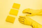 Hochwinkelaufnahme der Person in Gummihandschuhen und Schwämmen auf gelbem Hintergrund