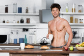 Muscular man smiling at camera while holding cup near breakfast on kitchen table