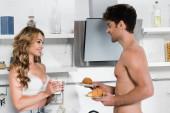 Sexy žena drží pohár a usmívá se na přítele bez košile s croissanty
