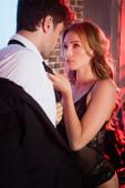 Szexi nő csipke kosztümben tartja nyakkendő barátja otthon este