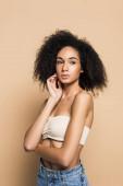 göndör fiatal afro-amerikai nő, csupasz vállakkal, félrenéz a bézs