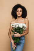 curly african american woman holding flowers isolated on beige