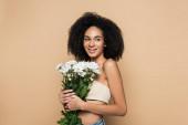 radostná africká americká žena drží květiny izolované na béžové