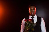 africký Američan ve formálním oděvu s vestou drží červené růže na černé
