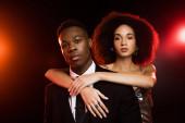 kudrnatý africký americký žena v šaty objímající přítel v obleku na černý
