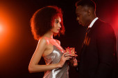 side view of african american man giving present to woman in dress on black