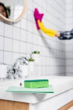 Sponge and rag on sink near woman cleaning tile in bathroom on blurred background stock vector