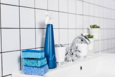 Blue sponges and bottle of detergent on sink in bathroom on blurred background stock vector