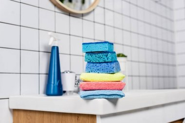 Colorful sponges on sink near detergent on blurred background in bathroom stock vector