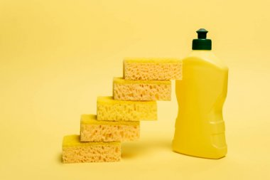 Sponges near yellow bottle of dishwashing liquid on yellow background stock vector