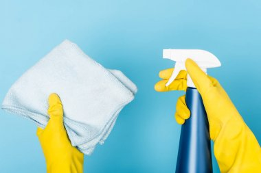 Cropped view of hands in rubber gloves holding detergent with sprayer and rag on blue background stock vector