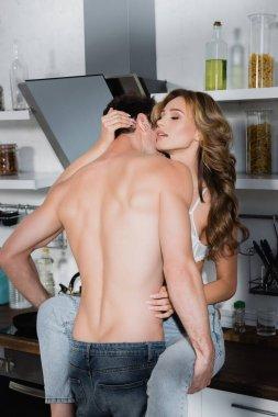 Shirtless man kissing sexy girlfriend on kitchen worktop stock vector