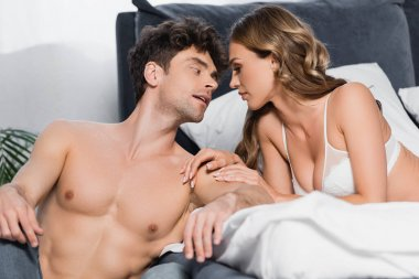Muscular man looking at seductive woman in bra on bed on blurred foreground stock vector