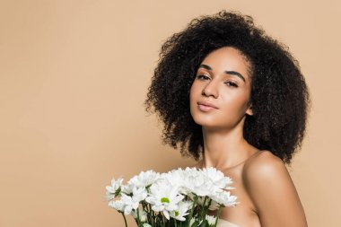 Curly african american woman with bare shoulders near flowers isolated on beige stock vector