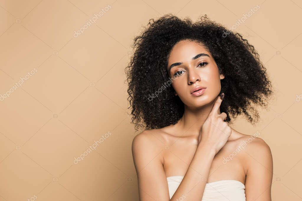 Young african american woman with bare shoulders looking at camera isolated on beige stock vector