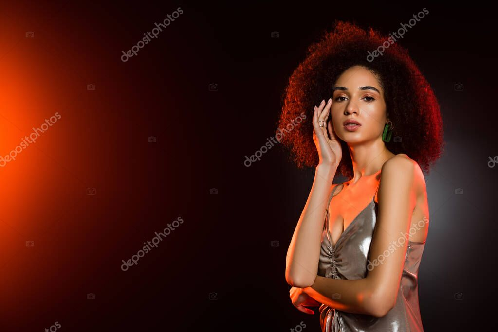 Elegant and curly african american woman in dress looking at camera on black stock vector