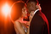 kudrnatý africký americký žena v šaty objímající muž na černošky