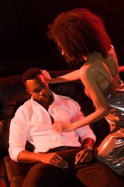 African american woman in dress seducing man in formal wear on black stock vector