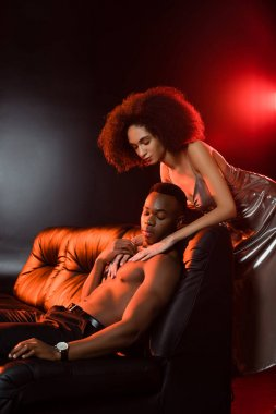 Sexy african american woman in dress seducing shirtless man on sofa and black background stock vector