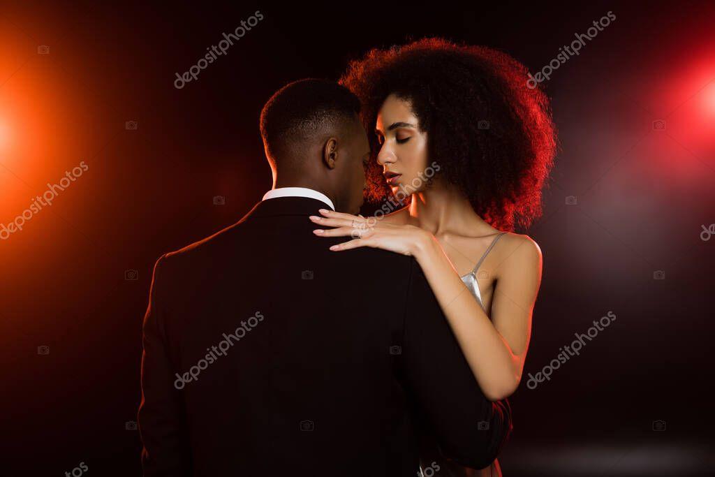 Elegant african american woman embracing man in formal wear on black stock vector