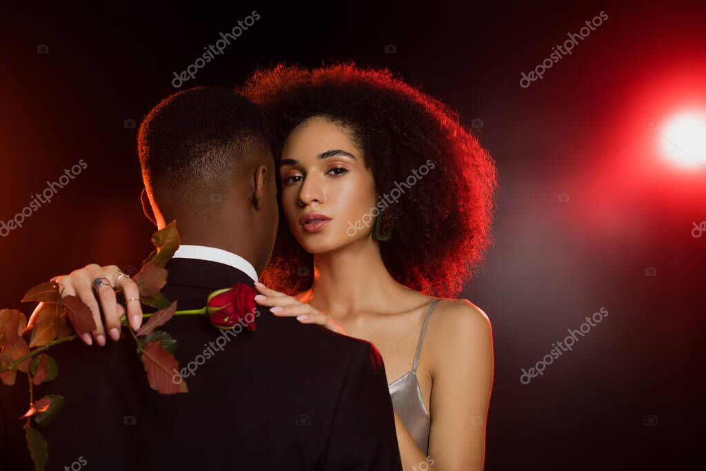 Elegant african american woman holding rose and embracing man in formal wear on black stock vector