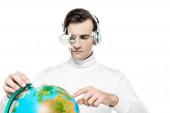 Cyborg muž v oku čočky a sluchátka ukazuje prstem na globus na rozmazané popředí izolované na bílém