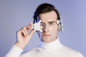 Cyborg man in headphones adjusting digital eye lens isolated on purple