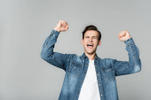Cheerful man showing yeah gesture isolated on grey