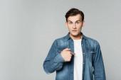 Junger Mann in Jeansjacke zeigt mit Finger auf sich selbst
