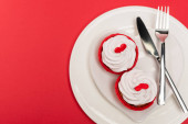 top view of cupcakes on plate with cutlery on red background