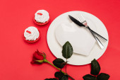 cupcakes near plate and rose on red background