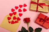 horní pohled na červená srdce, růže, obálky a dárkové krabice na růžovém pozadí