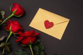 shora pohled na růže a valentinky obálka izolované na černé