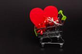 nákupní košík s valentinky dárky a srdce izolované na černé
