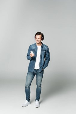 Smiling man using smartphone and headphones on grey background